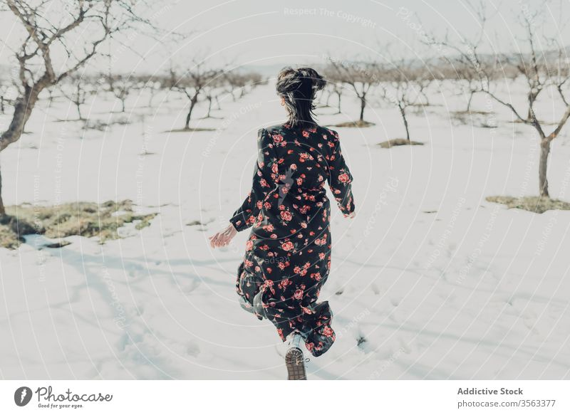Happy fashionable woman running on snow happy fun winter field cheerful trendy nature style female young joy relax freedom countryside excited carefree playful