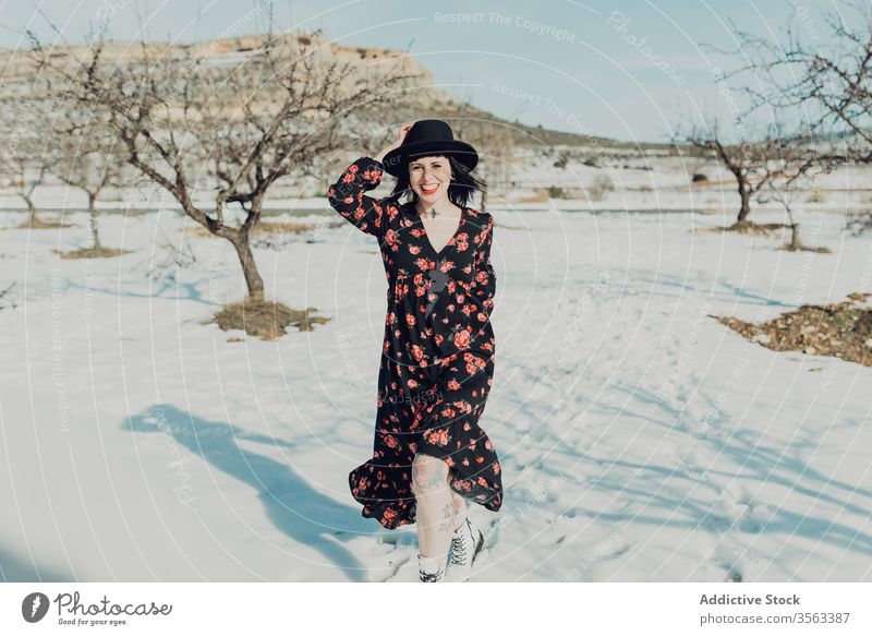Confident trendy woman standing in snowy field style confident nature attractive looking at camera modern fashion charming colorful defiant red young sensual