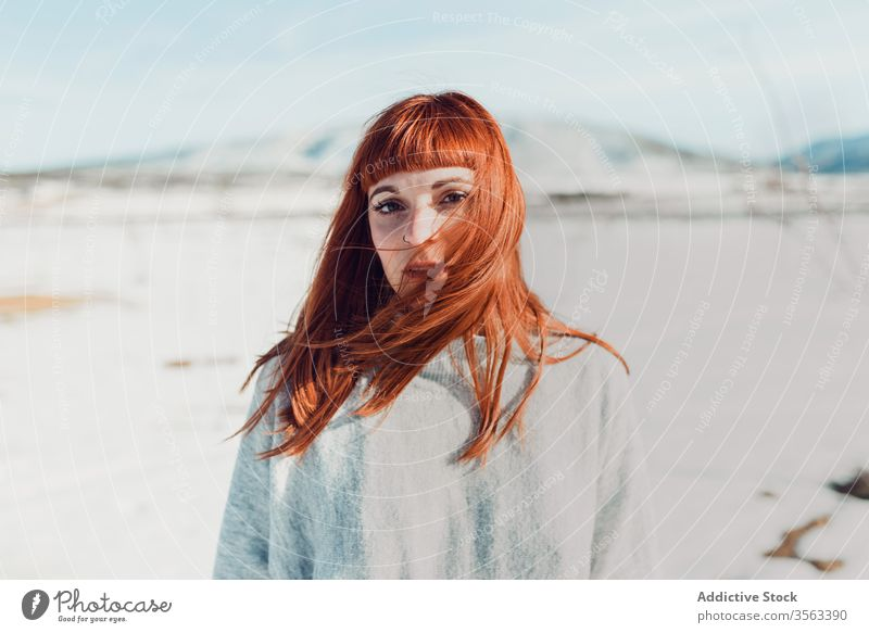 Sensual woman with red hair standing in snow field style trendy sensual redhead young nature attractive female ginger fashion modern charming elegant makeup