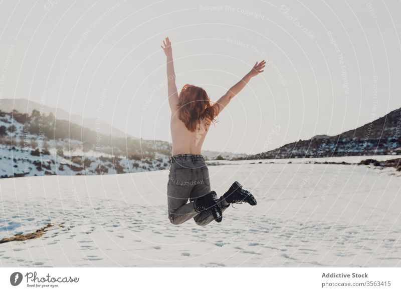 Happy topless woman jumping in snowy field happy carefree nude naked freedom enjoy winter nature energy female fun countryside cheerful young active adventure