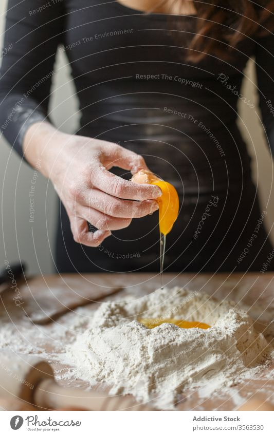Crop housewife adding eggs to flour while making dough raw break woman kitchen cook pastry prepare rolling pin ingredient process homemade table pasta food