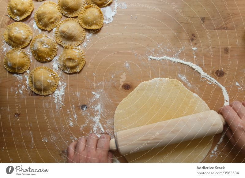Crop male cook rolling dough on table with ravioli rolling pin prepare circle raw person round wooden process kitchen food cuisine culinary homemade dish