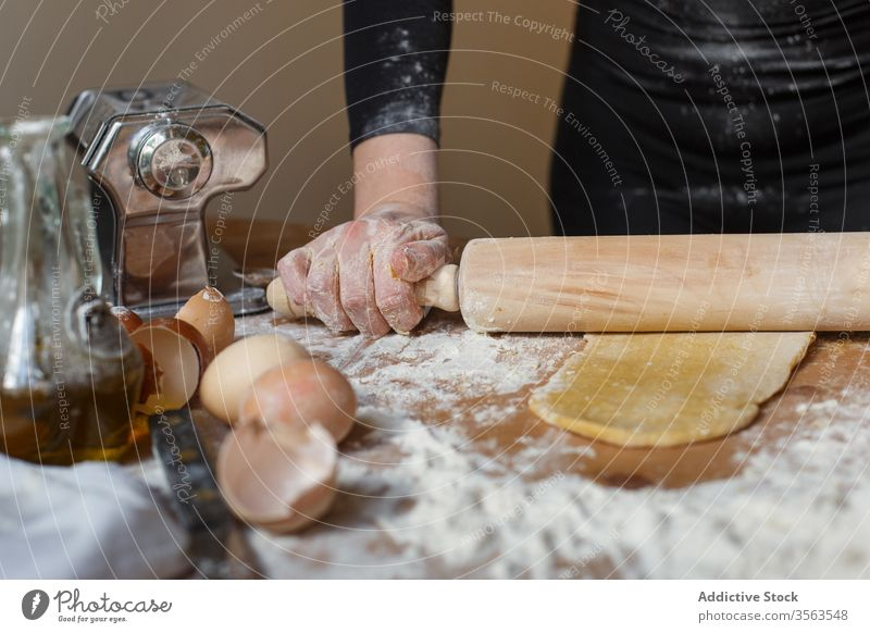 Crop lady rolling dough with rolling pin on table cook woman pastry elastic flour egg kitchenware jug eggshell glass prepare ingredient process pasta utensil