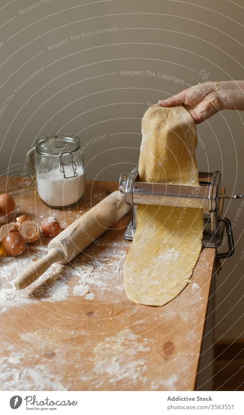 Anonymous female cook rolling dough while using pasta machine woman pastry elastic flour appliance kitchenware egg instrument glass whisk prepare eggshell