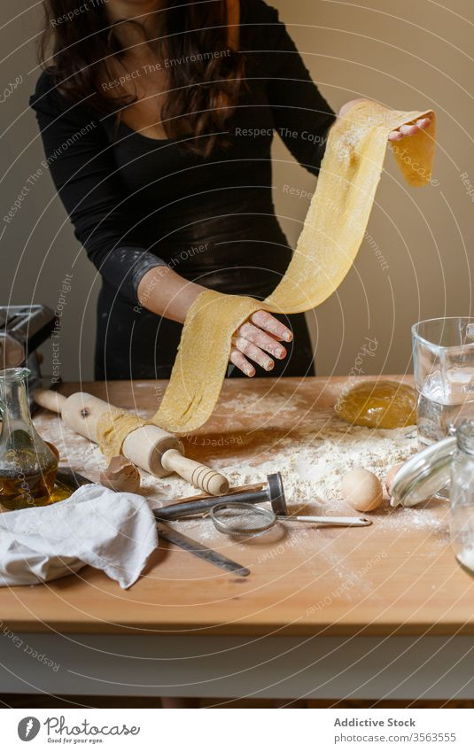 Faceless woman with rolled dough in kitchen elastic pasta homemade cook flour raw kitchenware dish egg prepare ingredient process rolling pin table utensil food