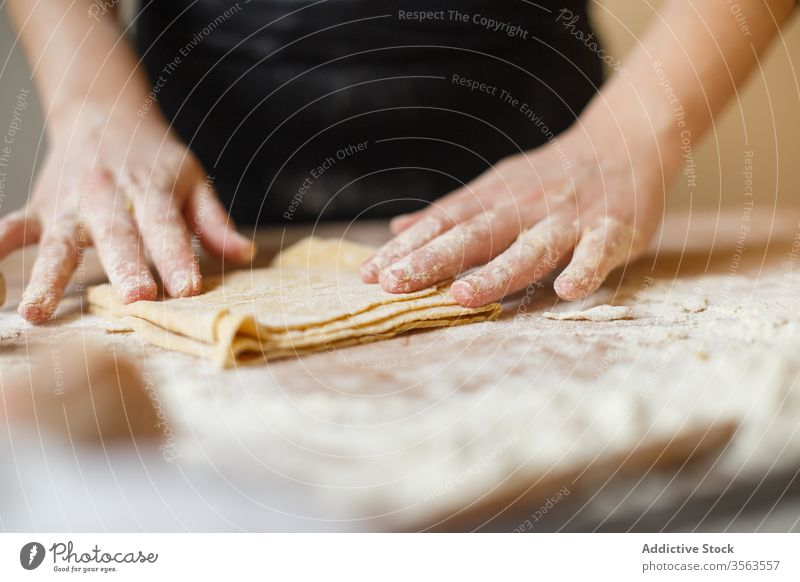 Crop person preparing making pasta with elastic dough fold layer cook roll flour prepare kitchen ingredient process table utensil food cuisine culinary homemade