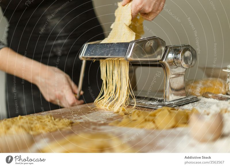 Faceless female cook cutting pastry using pasta machine woman roll stripe thin raw shape dough equipment device flour appliance kitchenware instrument prepare