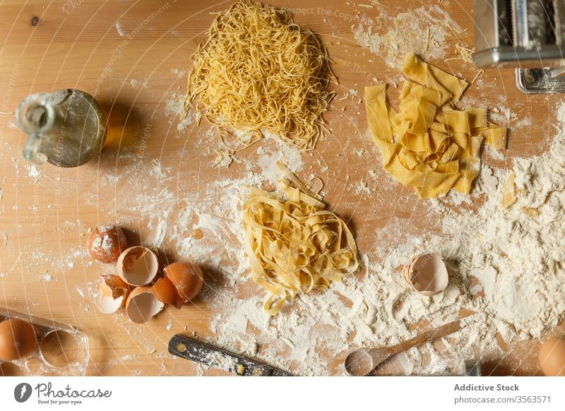 Composition of pasta and kitchenware on table raw flour utensil eggshell olive oil various shape dough pastry messy make device cookery prepare food spoon