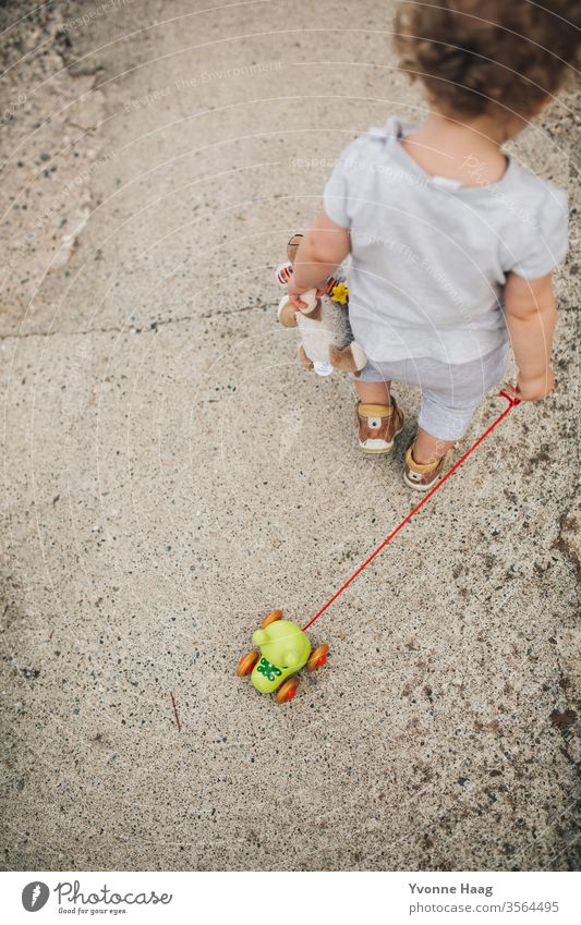 Toddler goes for a walk with her frog toy Beach Sky Coast Clouds Colour photo Nature Wind Exterior shot Landscape Water Bad weather Climate Environment Elements
