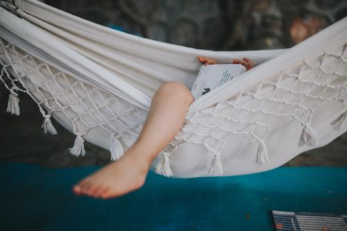 Child lies in a hammock and looks at a book Hawaii Gale Beach Sky Coast Clouds Colour photo Nature Wind Exterior shot Landscape Storm Water Bad weather
