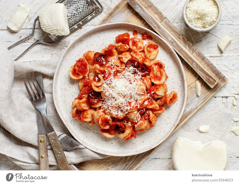 South italian  pasta orecchiette with tomato sauce and cacioricotta cheese apulia tomatoes sugo top view tray white grater wooden cooked cuisine diet dinner