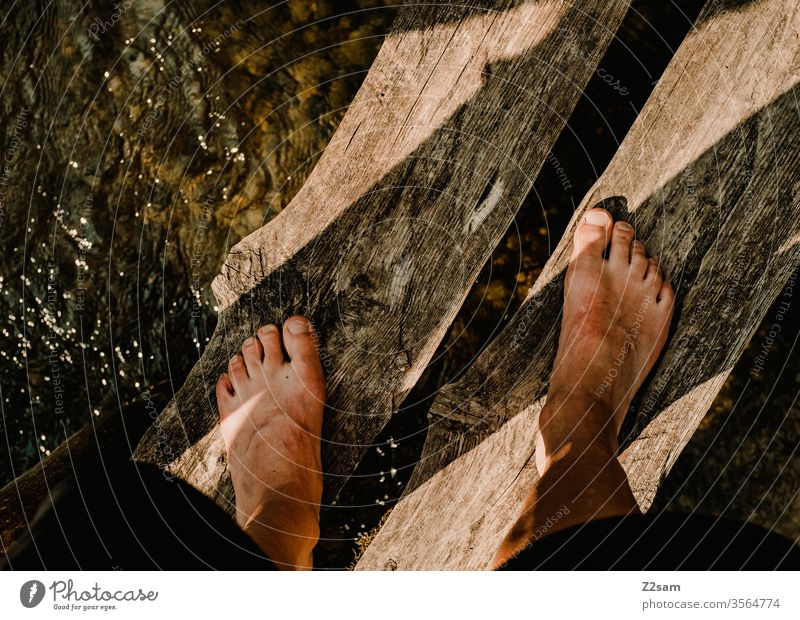 Man stands on wooden bridge over river foot Stand Water Nature River Barefoot Summer bathe Relaxation vacation Vacation & Travel Swimming & Bathing Colour photo