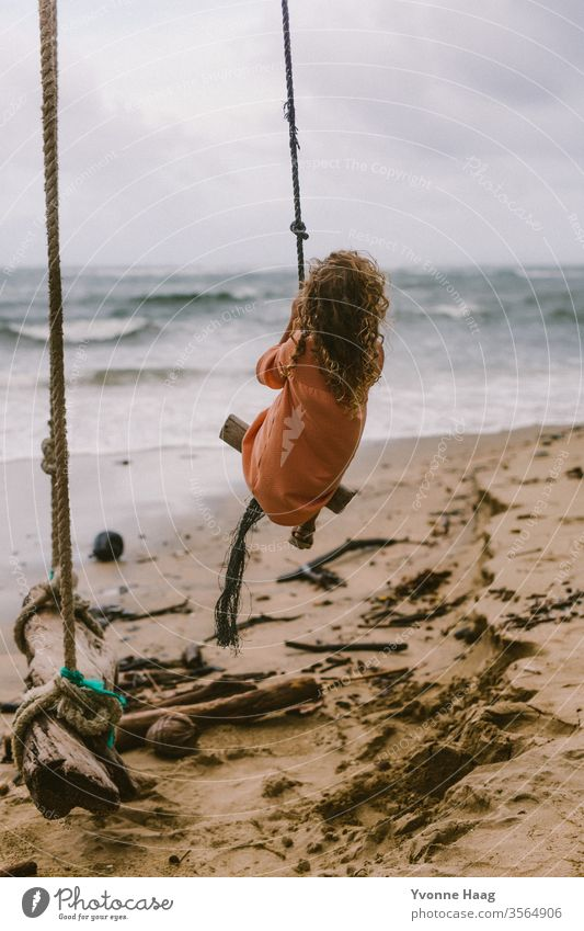 Girl sitting on a swing and swinging towards the sea Hawaii Hibiscus To swing Rocking Joy Playing Exterior shot Colour photo Swing Playground Infancy Day Child