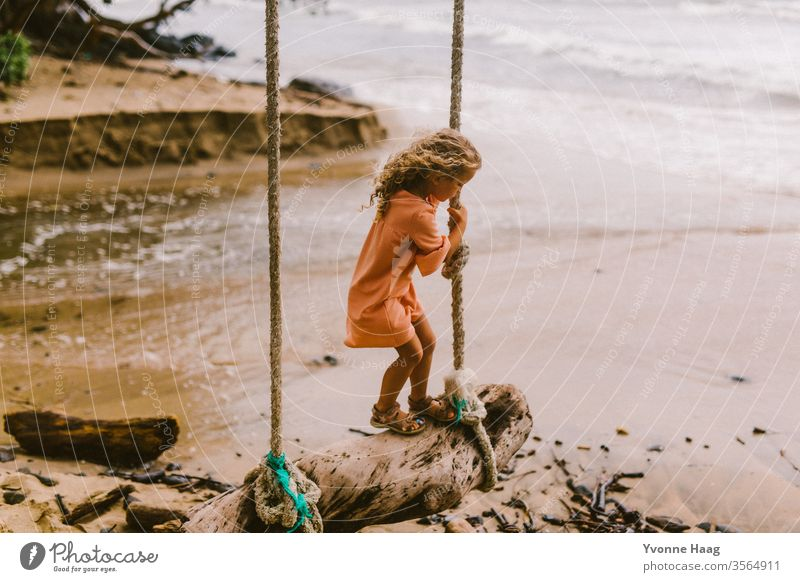 Girl stands on a swing and swings towards the sea Hawaii Hibiscus To swing Rocking Joy Playing Exterior shot Colour photo Swing Playground Infancy Day Child