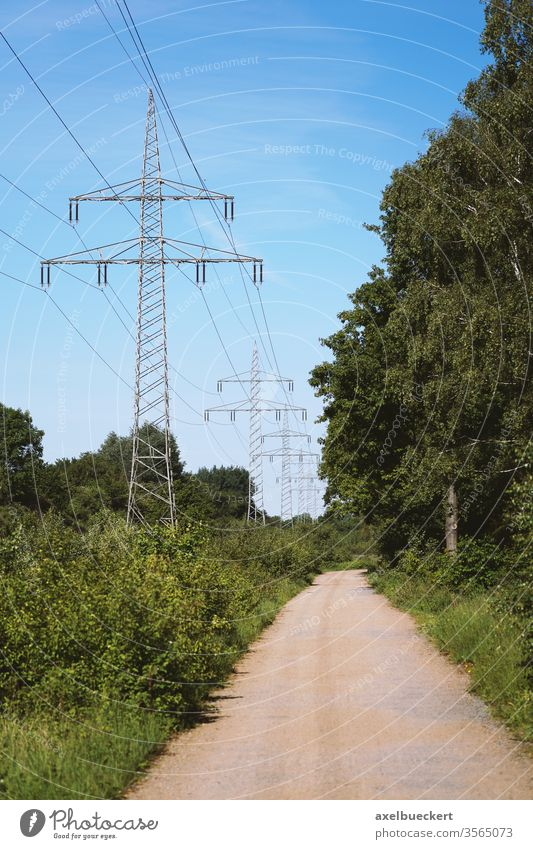 transmission line or overhead power cable along rural dirt track path through countryside high-voltage electricity pole pylon landscape tower nature road