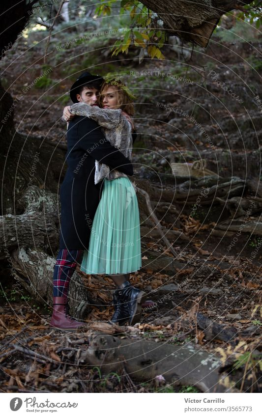 A young boho couple hugging in a woods background joy park fun deer leisure pretty cool stylish autumn leaves dress romance country relationship trendy freedom