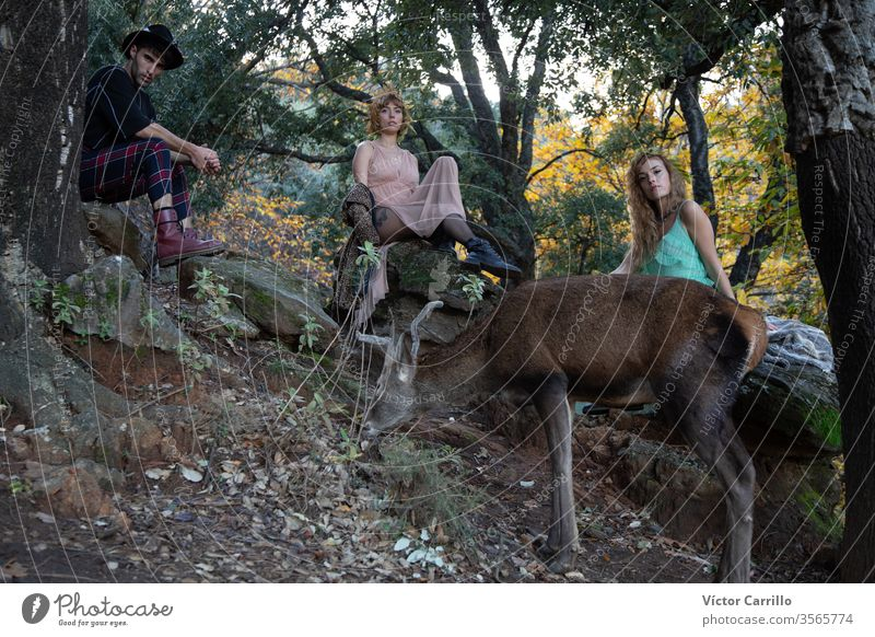 Two beautiful bohemian girls and a young man with a deer in a forest background joy park fun leisure pretty cool stylish autumn leaves dress romance country