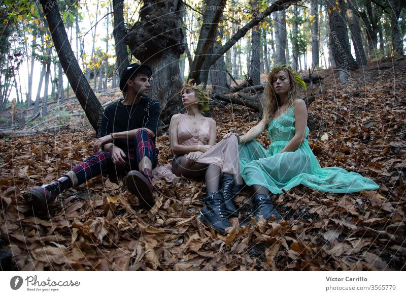 Three young bohemian friends in a forest natural pretty wild spiritual freedom person stylish green wild animals hair country romance dress beauty happy smile