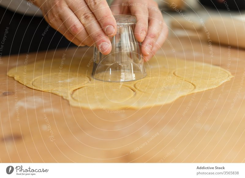 Anonymous male cook using glass for cutting round form for ravioli cutter dough ingredient press rolling pin circle table wooden prepare process man kitchen
