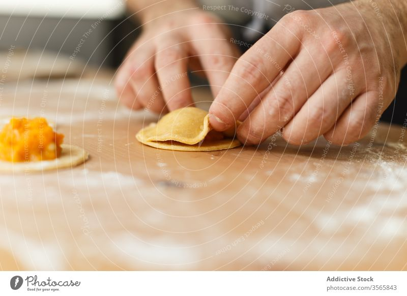 Crop person stuffing ravioli with pumpkin filling dough prepare circle cook table round wooden process kitchen food cuisine culinary homemade dish recipe