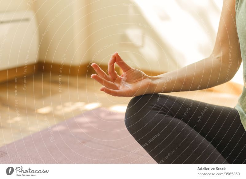 Crop woman in Lotus pose on mat yoga lotus pose mudra gesture exercise padmasana sportswear female calm practice mindfulness silent serene tranquil focus