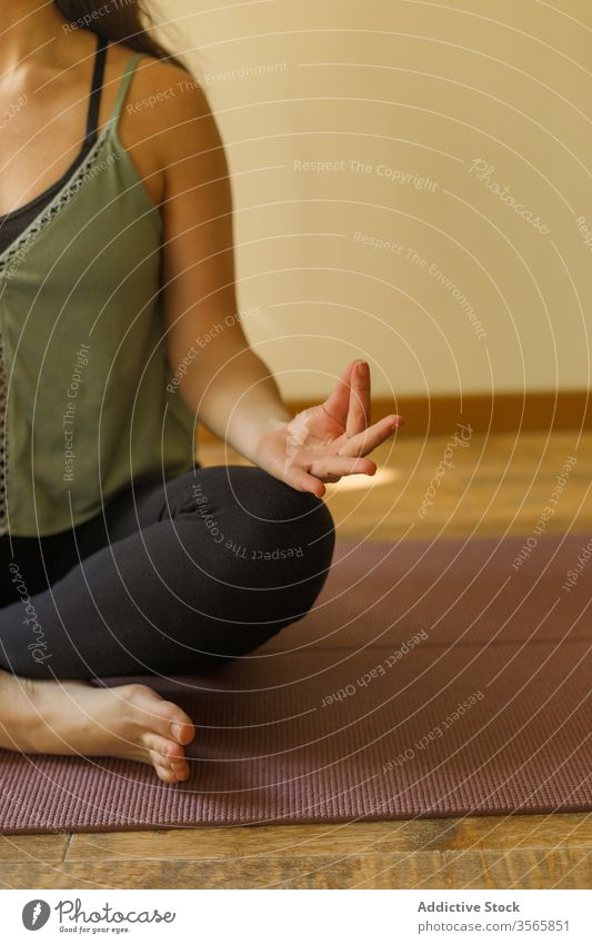 Crop woman in Lotus pose on mat yoga lotus pose mudra gesture exercise padmasana sportswear female calm practice mindfulness silent serene tranquil focus