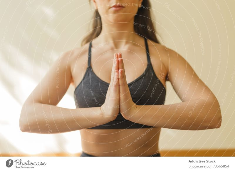 Tranquil woman meditating in Lotus pose lotus pose meditate yoga namaste padmasana mindfulness tranquil focus home female concentrate exercise mat training