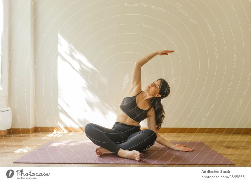 Flexible woman doing side bend and practicing yoga practice exercise flexible mindfulness serene sukhasana living room female stretch home tranquil focus