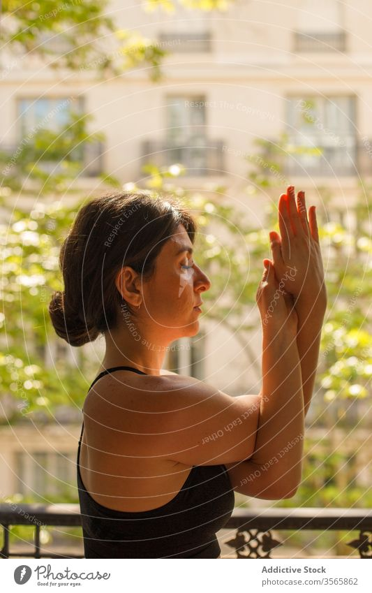 Calm female standing in eagle pose during yoga practice in summertime woman home meditate asana balcony calm peace mindfulness zen healthy lifestyle vitality