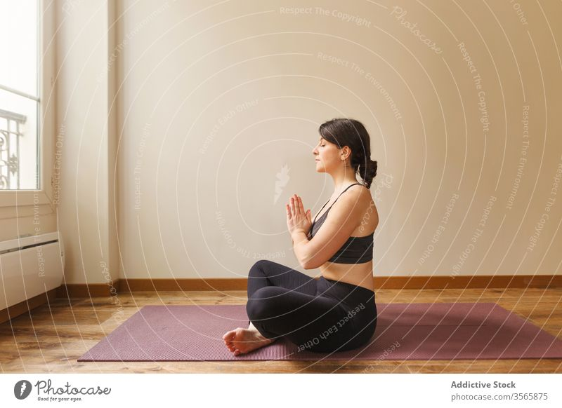 Tranquil woman meditating in Lotus pose lotus pose meditate yoga namaste padmasana mindfulness tranquil focus home female concentrate exercise mat training