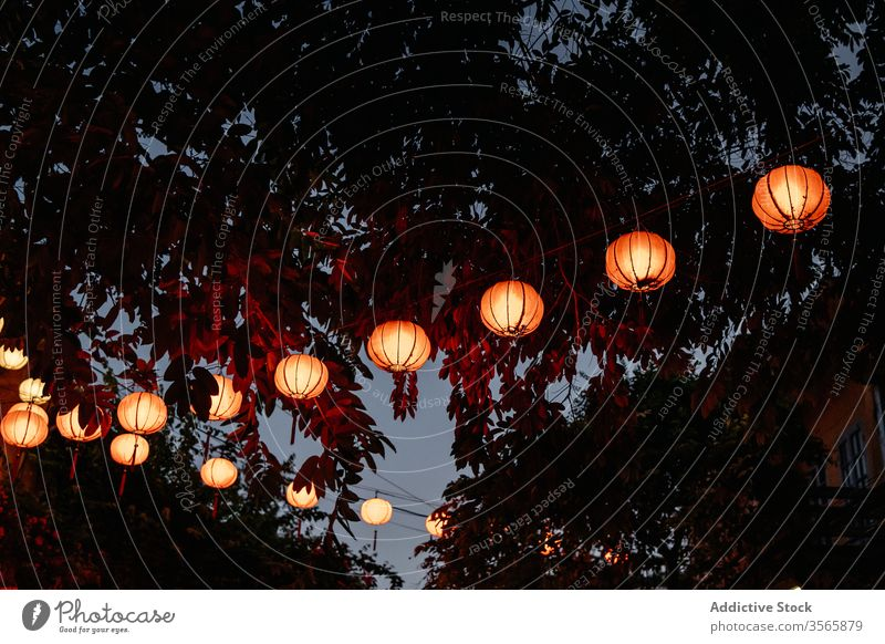 Asian paper lanterns glowing on street in evening illuminate asian festive oriental culture tradition hang decoration creative vietnam luminous garland dark