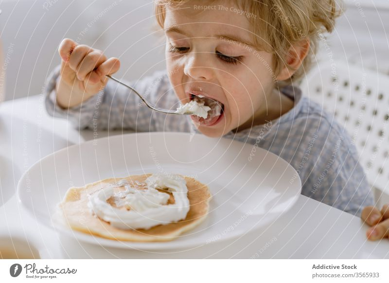 Little child eating pancake with whipped cream kitchen adorable kid delicious breakfast bright food table sit childhood tasty meal home nutrition morning sweet