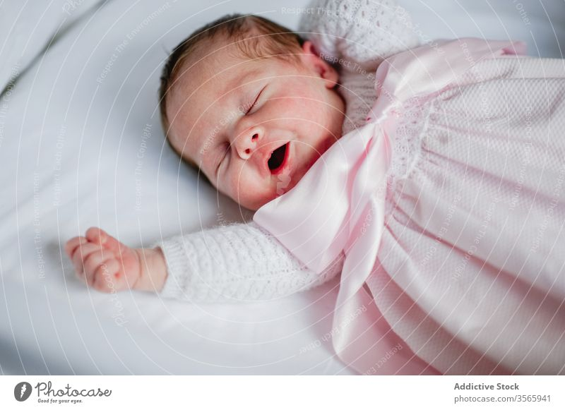 Newborn girl yawning in crib newborn baby cot adorable lying sleep cute cozy dress infant innocent child rest nap relax babyhood tranquil serene peaceful calm