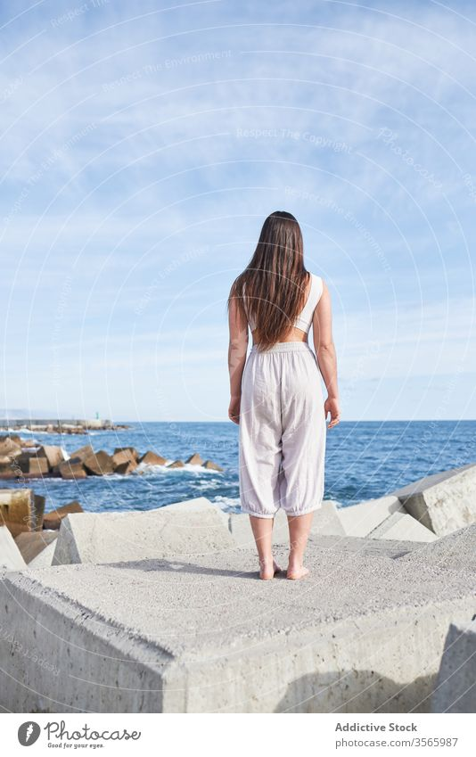 Anonymous modern woman standing on concrete block of breakwater sea harmony coast contemporary concept stone construction energy physical young pose female