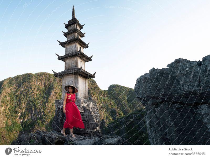 Female tourist near pagoda in Hang Mua hang mua woman travel buddhism tower landmark mountain landscape female mua cave vietnam asia top admire stand scenery