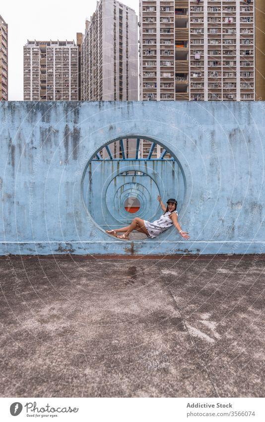 Woman sitting near walls with tunnel in Hong Kong woman passage street installation city unusual creative summer female shek kip mei hong kong round shape