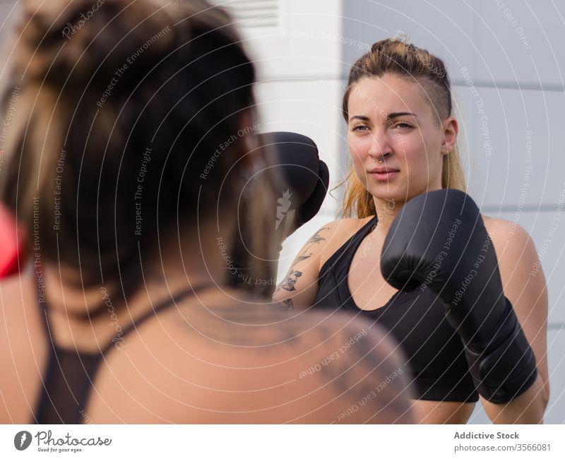 Determined female boxer training on street boxing glove sportswomen fighter punch workout determine fit sports ground active wear athlete body brutal attach
