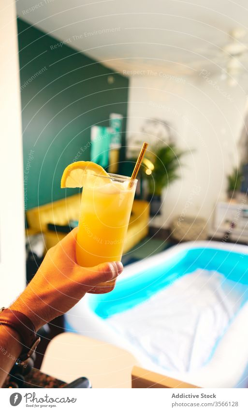 Crop man with glass of screwdriver drink summer home self isolation social distancing cocktail having fun party pool stay at home secure orange fresh slice male