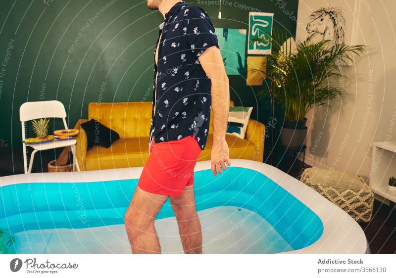 Man in inflatable pool during home party man stay at home summer apartment creative self isolation having fun water male shorts shirt social distancing outfit