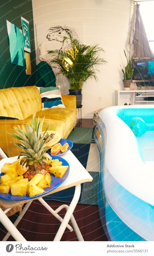 Interior of living room with inflatable pool party tropical stay at home self isolation fruit interior social distancing apartment having fun fresh creative