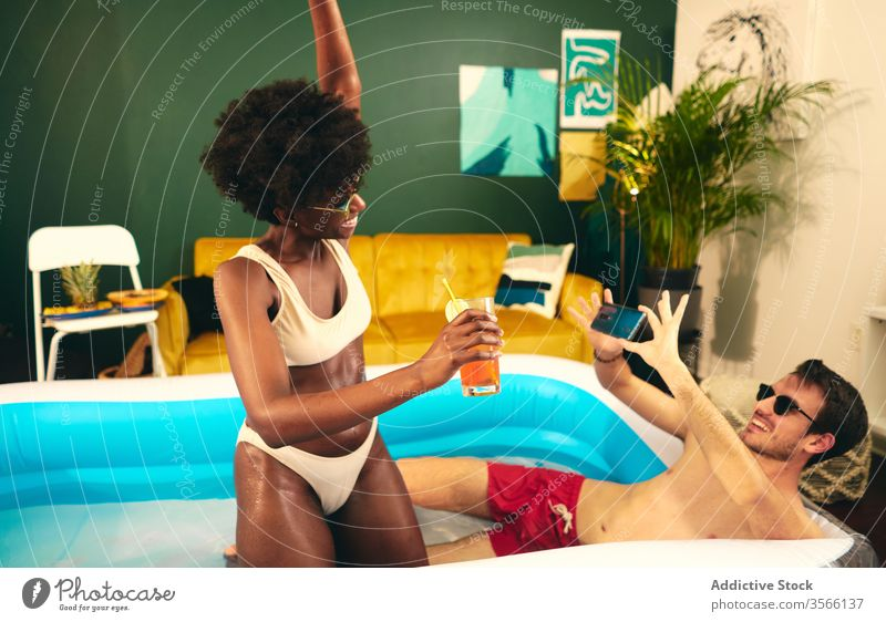 Content multiethnic couple taking photos and relaxing in pool take photo inflatable party stay at home cocktail having fun smartphone using self isolation