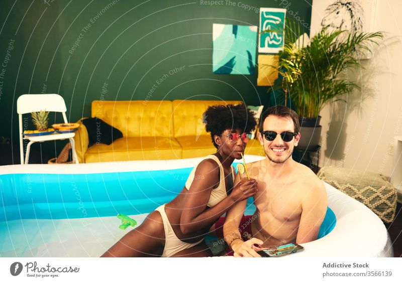 Content multiethnic couple resting in inflatable pool party stay at home content having fun self isolation in love social distancing water together multiracial