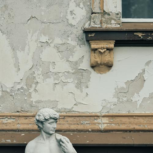 Head of a male statue in front of a facade with flaking paint and stucco detail of a window Facade Statue Roman Rome Flake off Brown Gray Old Window slice