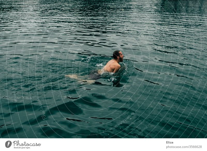 A man swimming in cold water be afloat Water chill chilly Ocean Lake bathe Blue Summer Swimming & Bathing brown-haired vacation Threat take a breath peril