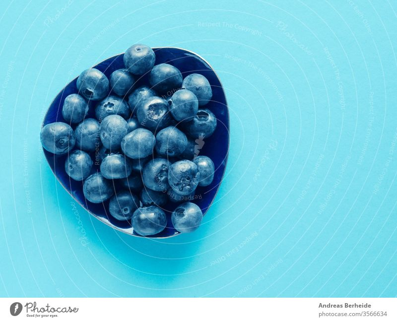 Tasty organic blueberries on a blue paper background antioxidants detox top view wet juice health vitamin nutrition dieting heap closeup harvest bio crop eating