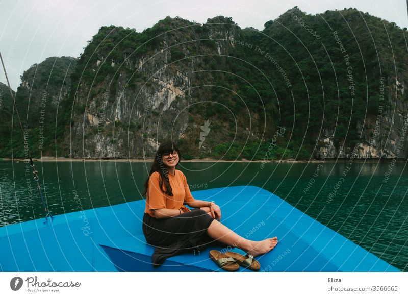Young woman sitting at the bow of a boat and laughing into the camera. Halong Bay in Vietnam. Woman Laughter vacation travel ship Trip Tourist Attraction