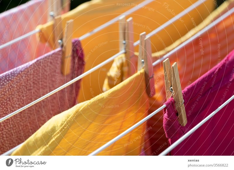 Summer laundry - clothes in yellow and pink hang on the clothes rack Laundry garments clothespin Hallstand Yellow Pink Dry Clothesline Washing day Household