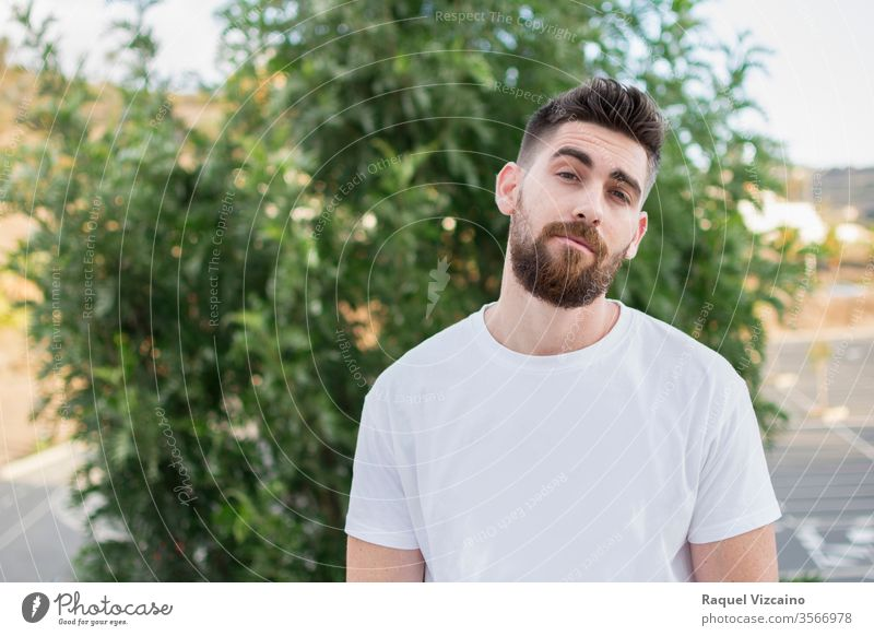 Handsome man with a beard and white t-shirt outdoors. portrait young handsome happy smiling person people park smile casual guy face men outside green boy one