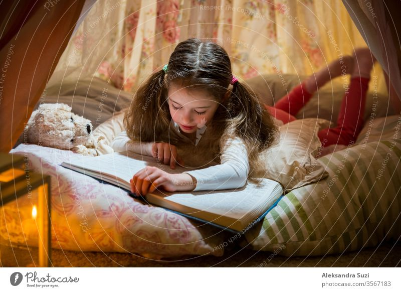 Cute little girl lying on pillows in homemade pink tent with flowers, read big book with interest and attention. Cozy stylish room. social distancing quarantine