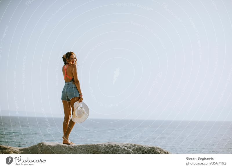 Young woman in bikini standing on rocks by the sea adult attractive beach beautiful blue brunette caucasian coast day female greece hair holiday leisure